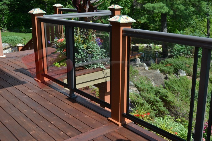 This image features a close-up of a railing system with aluminum and glass panels, wood posts, and the 6x6 Titan Post Anchor™.
