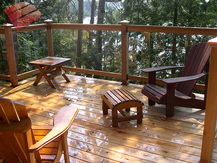 This outdoor deck blends into its forest setting, looking like it naturally belongs. The dark earthy tones of the wood complements the trees and surrounding nature.