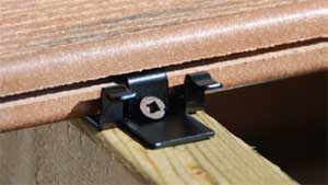 A close up view of a hidden fastener deck clip and grooved composite board