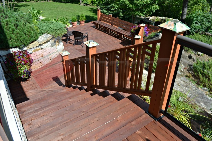 A top down view of stairs connecting a multi-level deck. This beautifully crafted deck features aluminum with glass panels and wood posts with 6x6 Titan Post Anchors™