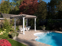 White pergola in front of a pool