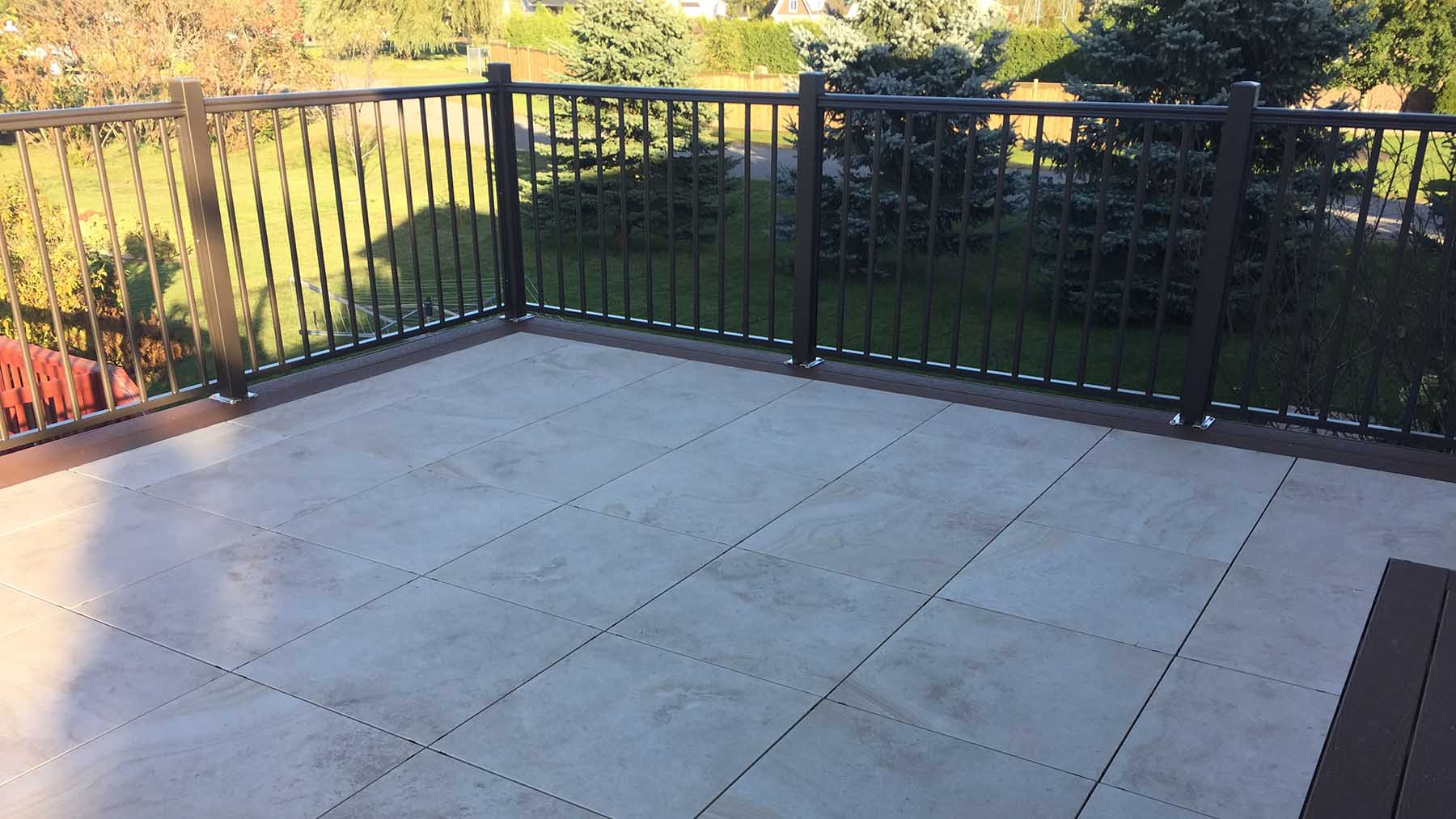 Silca grid below stone pavers and framed by composite decking.