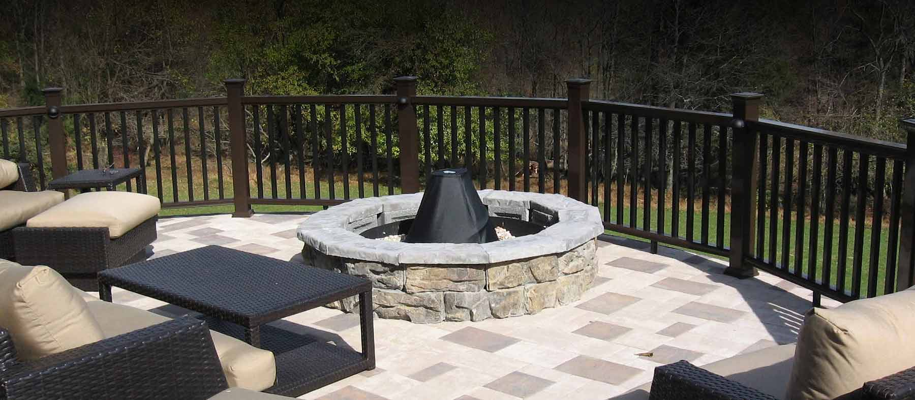 A wood framed elevated deck with patio paver stones and traditional railing.