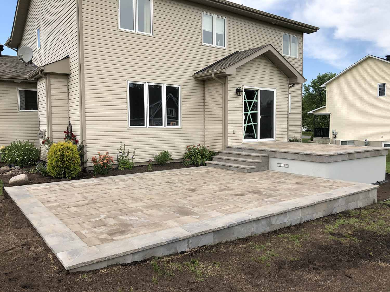 Multi level framed deck with paver stone surface and fascia board.