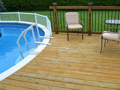 Treated wood decking against round above ground pool